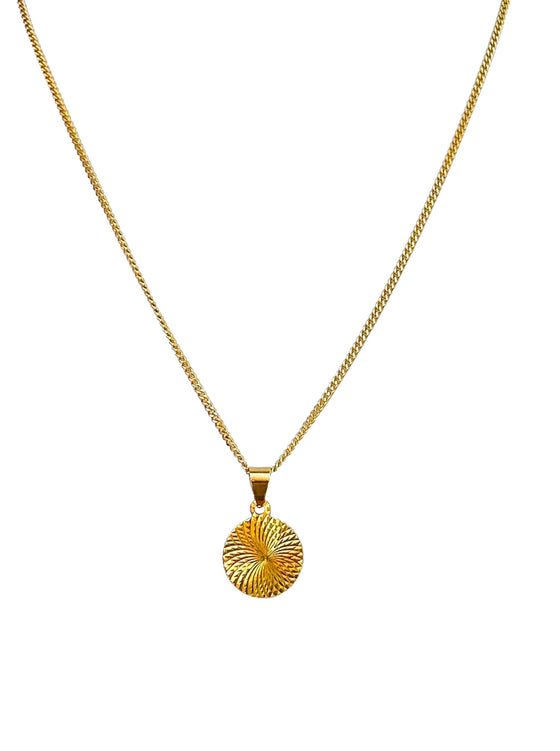 A gold chain with a small coin pendant that has swirls on it made by Meghan Bo Designs lays on a flat white surface.