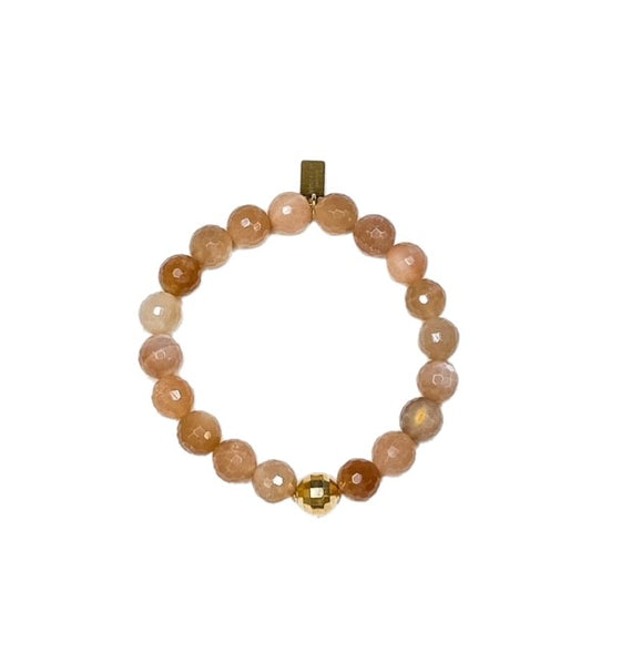 A peach colored beaded stretch bracelet with a gold accent bead made by Meghan Bo Designs lays on a flat white surface.