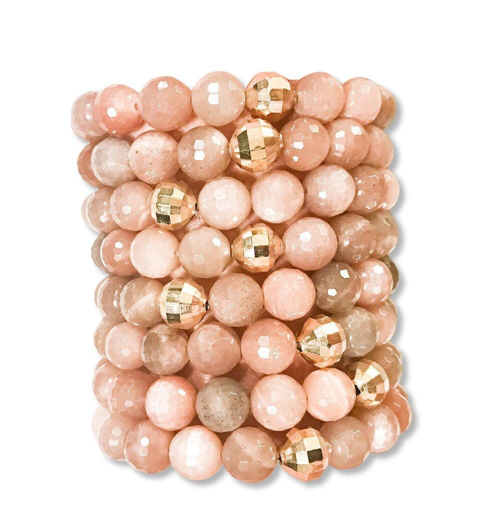 A stack of beaded stretch bracelets that have a light pink color bead and gold accent beads lay in a stack on a white background.