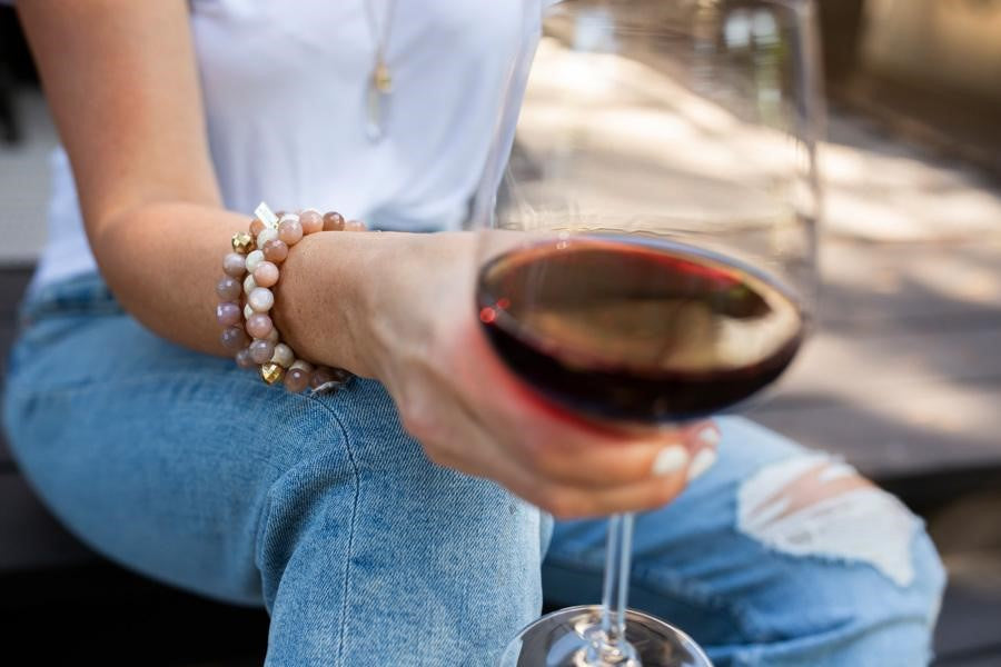 A woman wearing a white tee shirt and jeans sits with a glass of red wine and is wearing a stack of beaded stretch bracelets in pinks and whites made by Meghan Bo Designs.