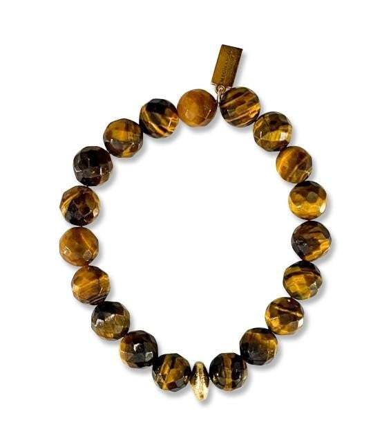 A beaded bracelet with faceted tiger eye beads and a gold accent bead made by Meghan Bo Designs lays on a flat white surface.