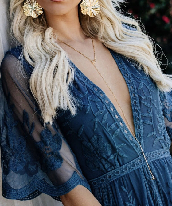 A woman with long blonde hair is leaning against a wall, she is wearing a blue lacey vici collection dress, gold earrings and a gold chain necklace with an adjustable toggle clasp made by Meghan Bo Designs.