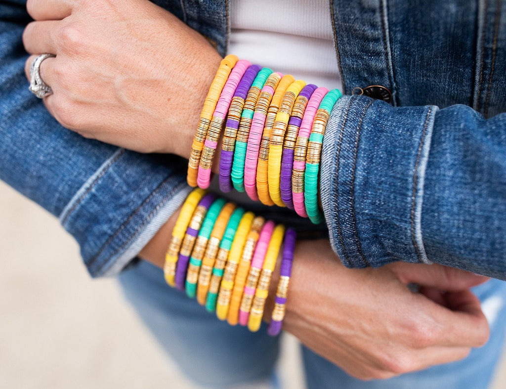 A woman wearing a denim jacket from Vici collection and jeans with a white shirt has her arms crossed and is wearing stacks of heishi beaded stretch bracelets in orange, pink, purplge, green, yellow and gold made by Meghan Bo Designs.