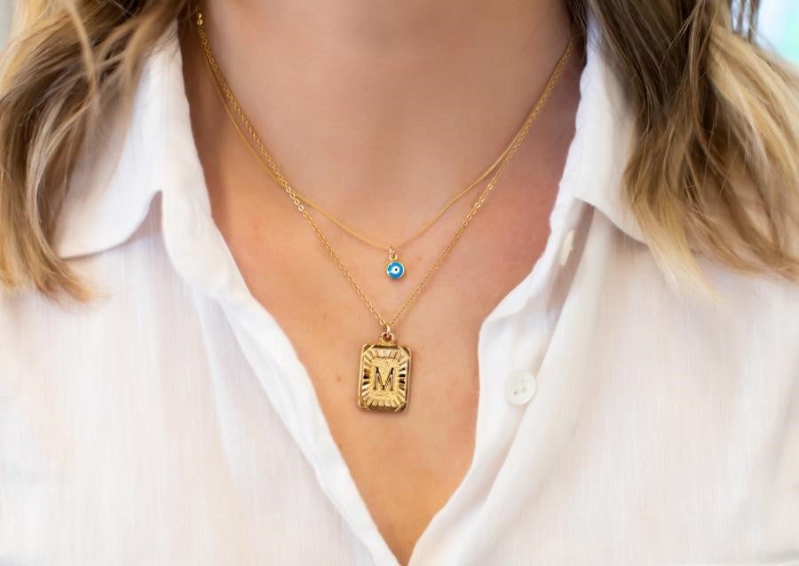 A woman wearing a white blouse is wearing two layered necklaces, one with with an initial pendant and the other has a small blue evil eye pendant made by Meghan Bo Designs.