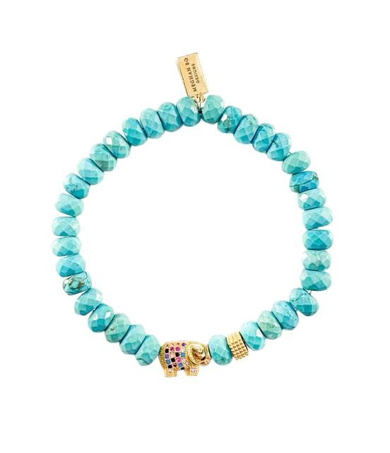 A bracelet with turquoise beads, a colored CZ elephant bead and a gold accent bead made by Meghan BO Designs lays on a flat white surface.