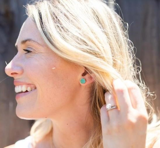 A woman with blonde hair is smiling and looking to the side, she has a solitaire diamond ring and turquoise stud earrings made by Meghan Bo Designs.