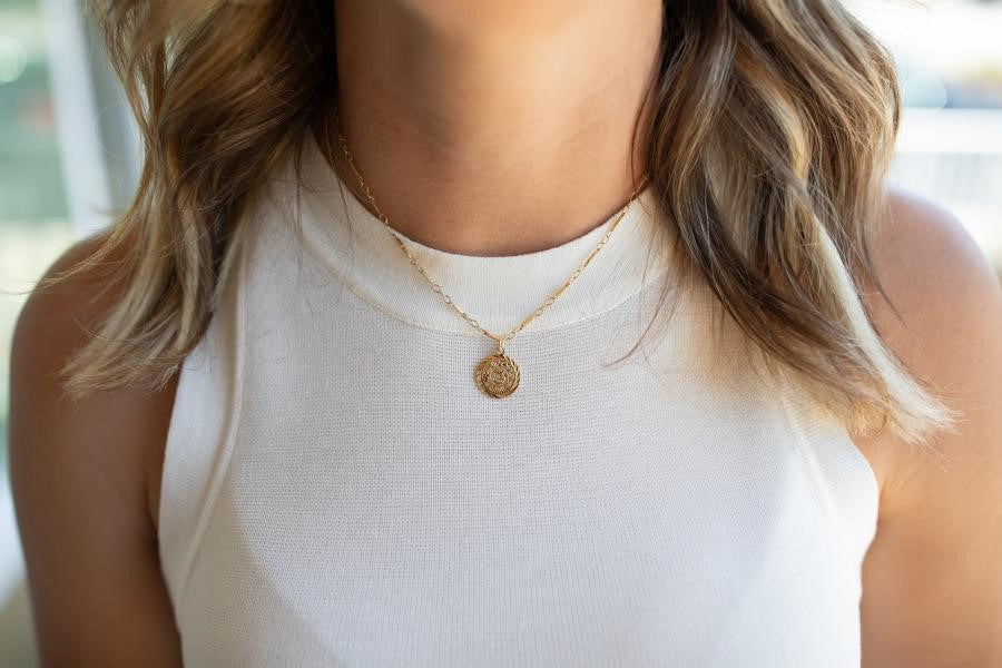 A woman with blonde wavy hair is wearing a white tank top by Vici Collection and is wearing a gold chain necklace with a small gold coin pendant made by Meghan Bo Designs.