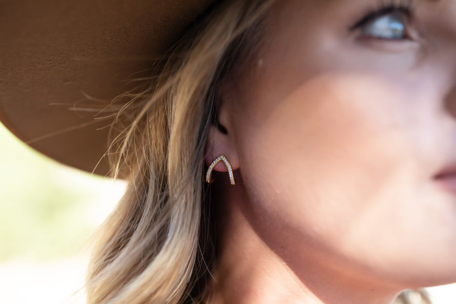 A woman with blonde hair is wearing a brown hat and looking off to the side, she is wearing stud cubic zirconia earrings made by Meghan Bo Desgins.