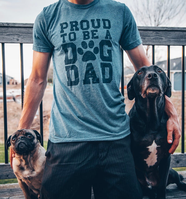 A Denim Heather colored unisex crew neck short sleeve tee shirt. Navy Front graphic reads Proud To Be A Dog Dad. The O in dog is replaced with a paw print.