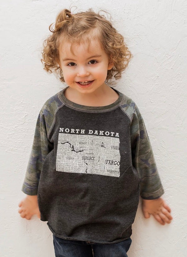 A Toddler sized Camo sleeved baseball tee with graphic of North Dakota and it's cities in it.