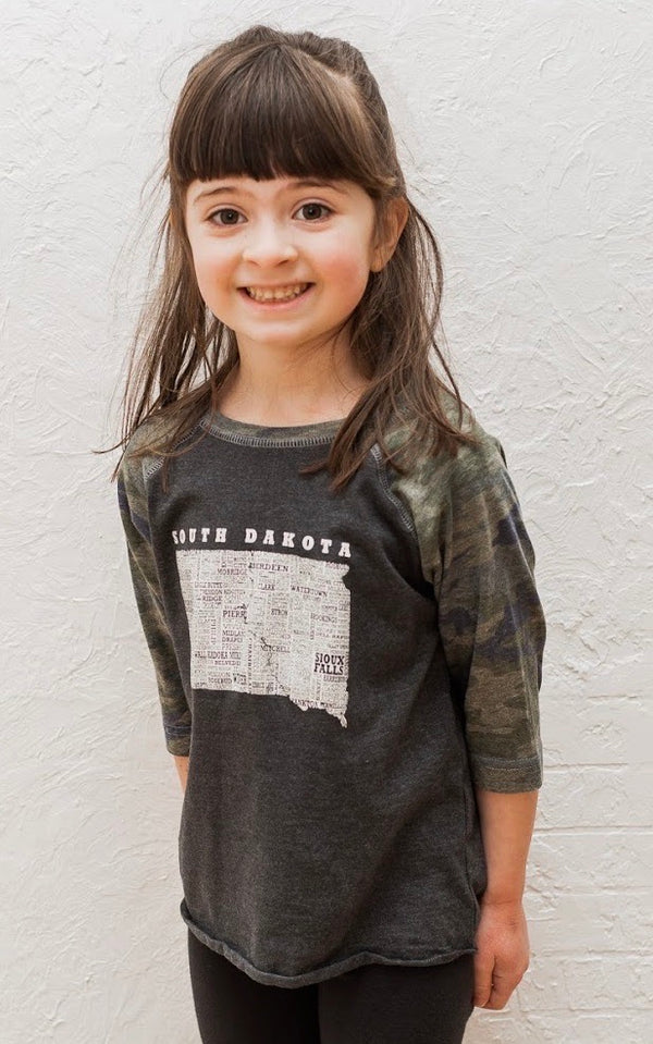 A grey Toddler sized baseball tee with camo sleeves and graphic of South Dakota and  it's cities on it.