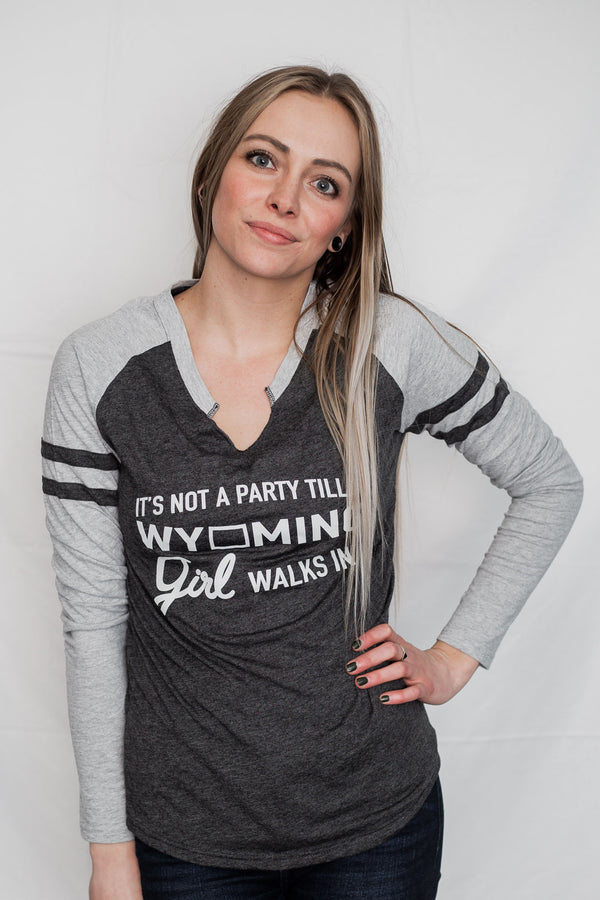 A jersey styled ladies long sleeve notched collar tee shirt with front graphic reads It's Not A Party Till A Wyoming Girl Walks In. Dark grey body with light grey sleeves.