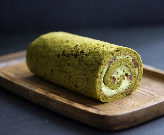 Thin matcha cake sheet spread with matcha red bean cream filling is rolled into classic delicious matcha green tea swiss roll cake