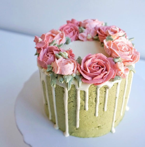 Delicous matcha cake topped with smooth matcha buttercream and roses