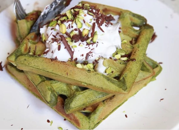Lovely luscious Matcha Waffle topped with vegan coconut whipped cream, shredded chocolates, and chopped pistachios