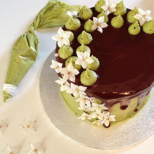 Matcha Chocolate Cake layered with jam and with a hint of coffee is coated with matcha buttercream and chocolate glaze