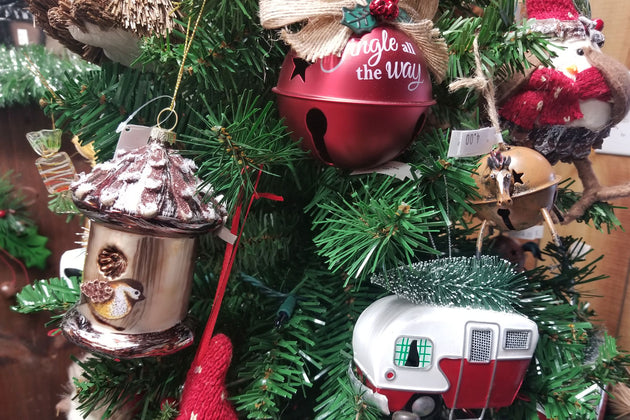 Christmas ornament of a bird feeder, holiday bell, and Rv on a christmas tree