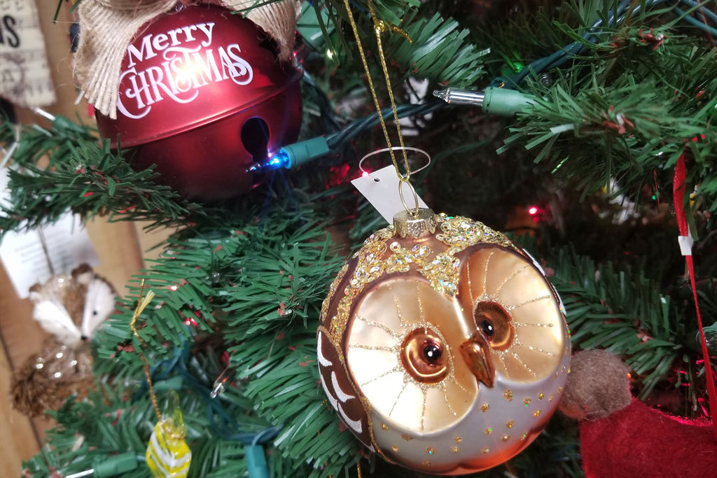 Christmas ornament of owl and holiday bell on a decorated christmas tree