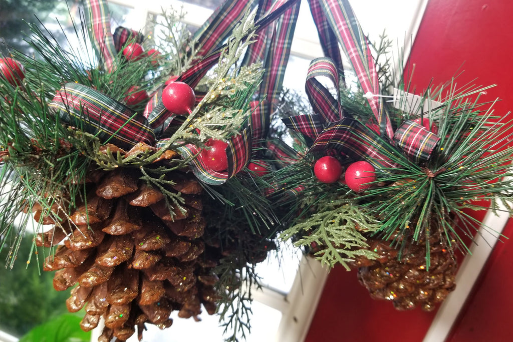 decorated large greenery pine cones with flanel ribbon, berries, and glitter