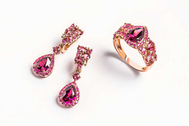 Jewelry gold set of ring and earrings with pink topaz on white background