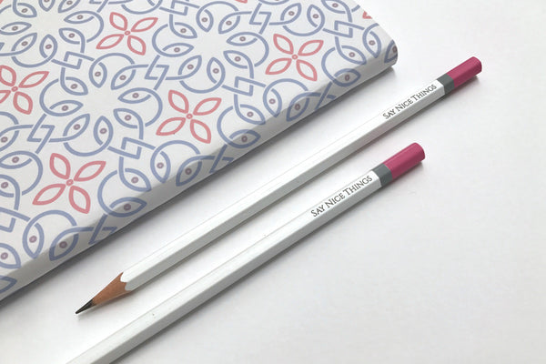 Image of two Say Nice Things pencils in white lay next to a Clover A5 journal