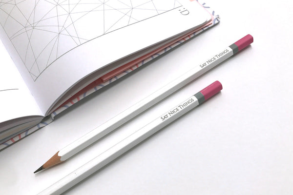 Image of two Say Nice Things pencils in white next to an open Say Nice Things journal