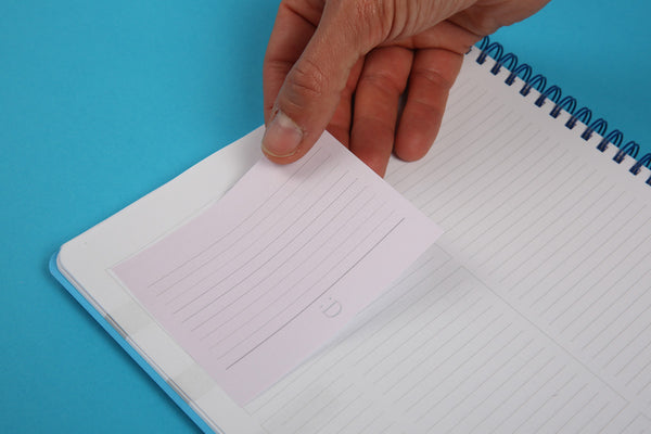 Image showing large sticky note from the Essentials notespod being positioned in the A4 notebook