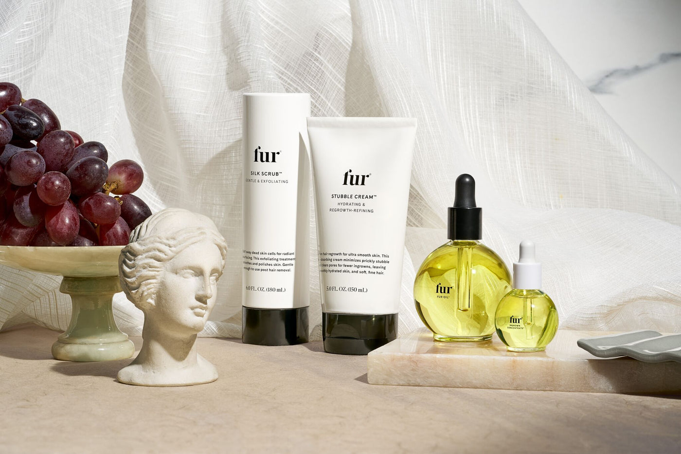 Fur Oil, Ingrown Concentrate, Stubble Cream, and Silk Scrub on a marble tray with grapes and a small statue head surrounding them set against a white curtain background.