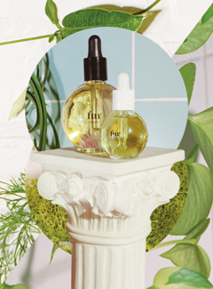 Fur Oil and Ingrown Concentrate bottles on top of a small pedestal with plants in the background.