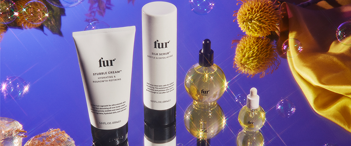 Stubble Cream, Silk Scrub, Fur Oil, and Ingrown Concentrate surrounded by plants and bubbles.