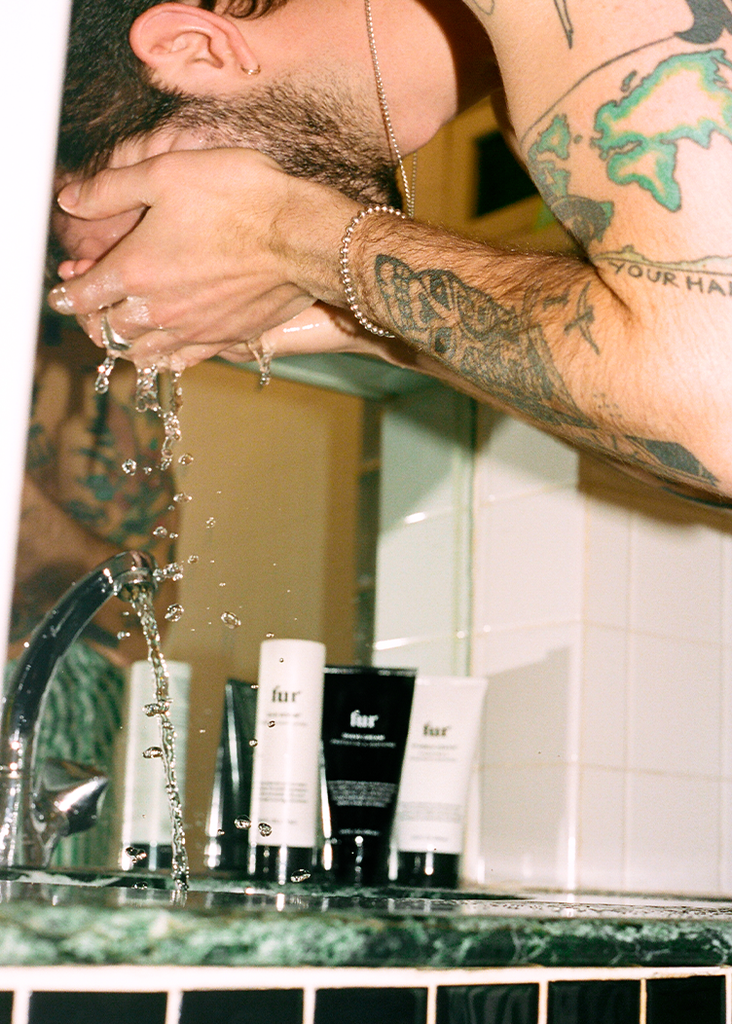 Man hunched over a sink splashing his face with water with Fur products in the background on the counter.