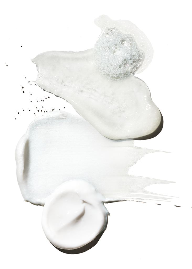Swipes of oil, lotion, and shaving cream against a white background.