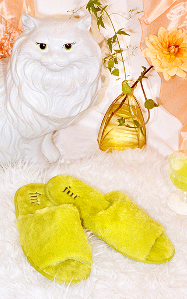 Furry green slippers on a carpet with a statue of a cat and plants in the backgorund.