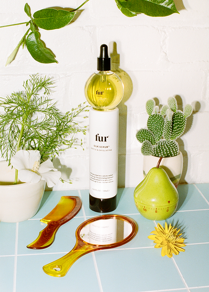 Fur Oil on top of Silk Scrub with a mirror, comb, and plants surrounding them.