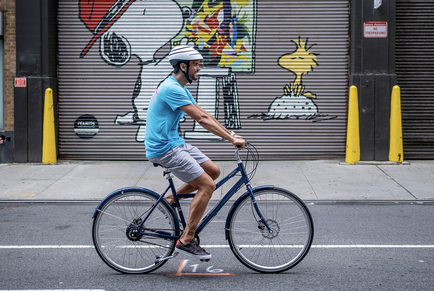 man with a blue shirt is riding with a step through bike