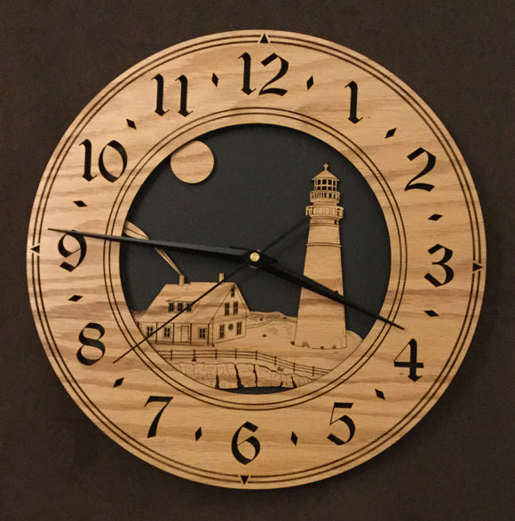 Round oak clock with a lighthouse, moon and lightkeeper's house lasered in the face against a black background - larger sizes