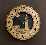 "Round oak clock with a lighthouse, moon and lightkeeper's house lasered in the face against a black background - 8"" size"