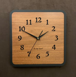 "This larger Walnut Classic clock has a walnut face surrounded by a black edge. The numbers are laser-cut through, showing the black background behind them. ""Blue Ridge Originals"" is lasered in small letters in the lower center of the clock."
