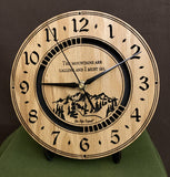 "Round oak clock with a mountain and the words, ""The mountains are calling and I must go"" lasered in the face - 8"" on easel"