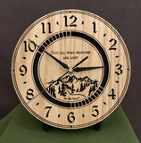 "Round Oak clock with a mountain and the words, ""Not all who wander are lost"" lasered in the face - 8"" on easel"