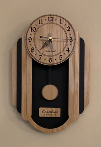 Oblong oak and black pendulum clock consisting of a round face and, under it to either side, 3 alternating oak and black rounded segments which decrease in size from front to back. The clock has a rounded bottom and a black background beneath the face. Front view, smaller sizes