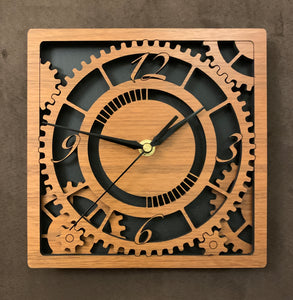 Square walnut clock with black background. The front shows a large single gear surrounded by smaller gears and partial gears, and the numbers 12, 3 , 6, 9. One layer down are two smaller gears. Larger sizes
