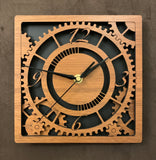 "Square walnut clock with black background. The front shows a large single gear surrounded by smaller gears and partial gears, and the numbers 12, 3 , 6, 9. One layer down are two smaller gears. 8"" size"