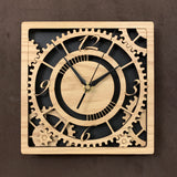 "Square oak clock with black background. The front shows a large single gear surrounded by smaller gears and partial gears, and the numbers 12, 3 , 6, 9. One layer down are two smaller gears. 8"" size"