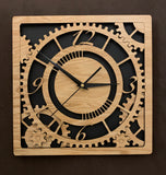 Square oak clock with black background. The front shows a large single gear surrounded by smaller gears and partial gears, and the numbers 12, 3 , 6, 9. One layer down are two smaller gears. Larger sizes