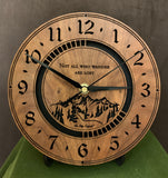 "Round walnut clock with a mountain and the words, ""Not all who wander are lost"" lasered in the face - 8"" on easel"