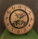 "Round walnut clock with a mountain and the words, ""The mountains are calling and I must go"" lasered in the face - 8"" on easel"
