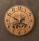 "Round walnut clock with a mountain and the words, ""The mountains are calling and I must go"" lasered in the face - 6.5"" size"