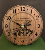 "Round walnut clock with a mountain and the words, ""The mountains are calling and I must go"" lasered in the face - 6.5"" on easel"