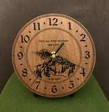 "Round walnut clock with a mountain and the words, ""Not all who wander are lost"" lasered in the face - 6.5"" size on easel"